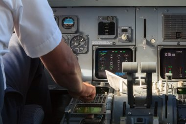 Apilot checking instruments in a plane cockpit