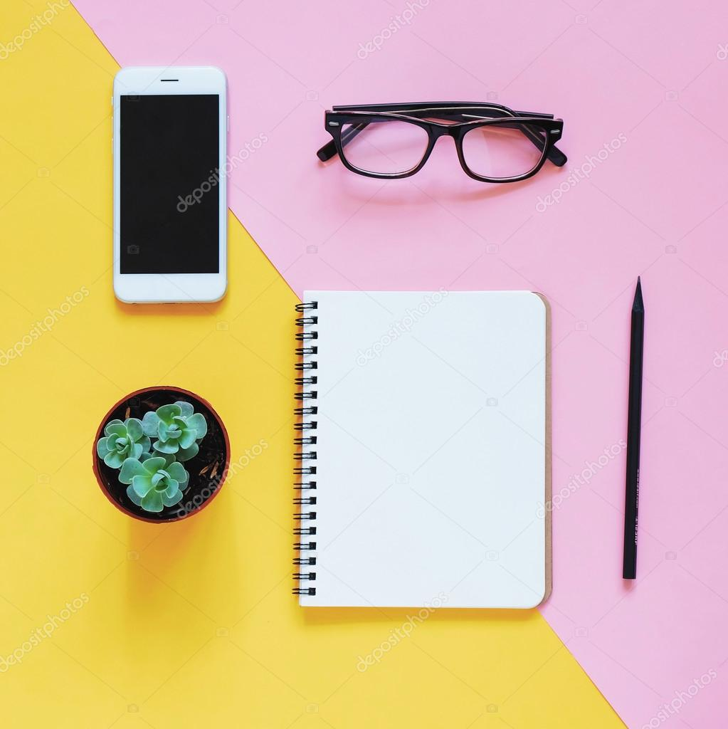Workspace desk with smartphone, eyeglasses, cactus