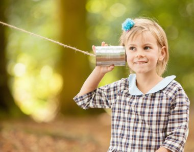 Girl listening on a tin can communicator.