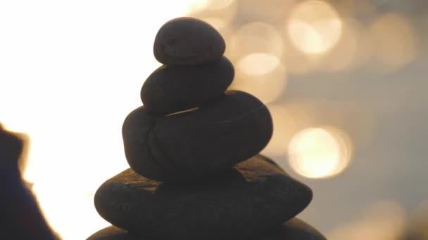 Sziluett kavicsos kövek hátterében naplemente és a tenger. Az egyensúly fogalma.