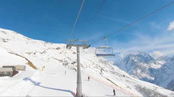 Winterpanorama mit Skiliften und schneebedeckten Bergen an einem sonnigen Tag.