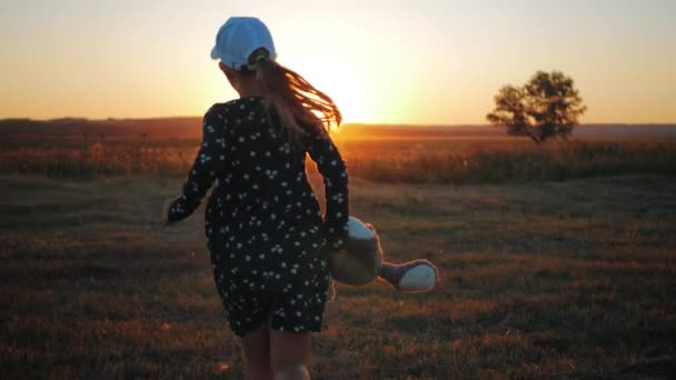 Little girl in dress holding teddy bear toy at sunset. Concept of a child dream.