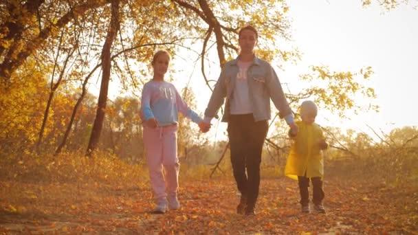 Mutter und zwei Kinder spazieren durch den Park und genießen die herrliche herbstliche Natur. Glückliche Familie beim Herbstspaziergang.