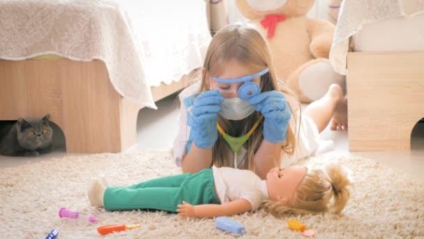 Krásná holčička hraje doktory s panenkou doma.