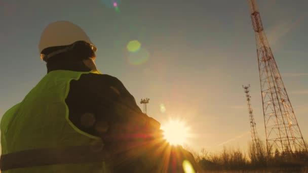 Silueta starší inženýr pracující se satelitním příjmem telekomunikační sítě v telekomunikační věž na pozadí.