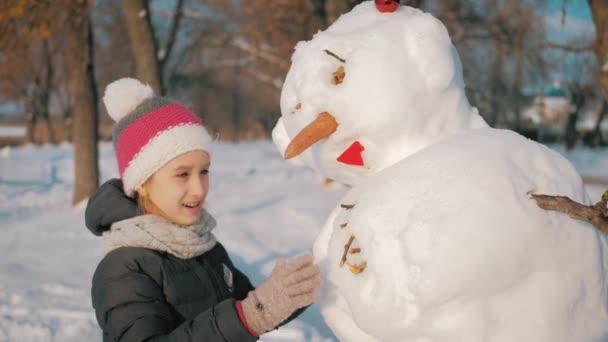 Šťastná dívka staví sněhuláka v zimním parku. Koncepce zimních prázdnin a Vánoc.