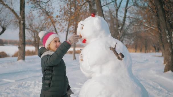 Dívka vloží nos na sněhuláka. To dítě si hraje se sněhulákem. Zimní šťastný čas, dítě na sněhu.