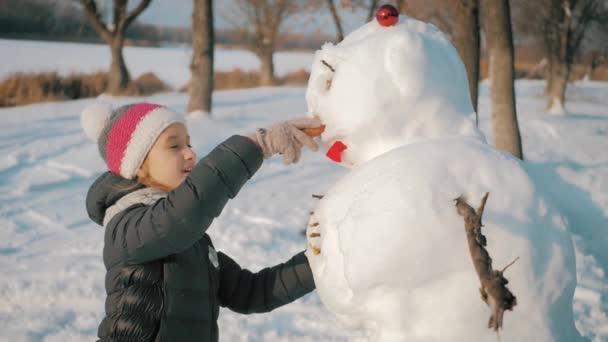 Mädchen setzt dem Schneemann eine Nase auf. Das Kind spielt mit einem Schneemann. Winterfreudige Zeit, Kind auf Schnee.