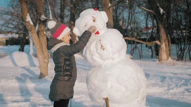 A lány beleüti az orrát a hóemberbe. A gyerek hóemberrel játszik. Tél boldog idő, gyerek a hóban.