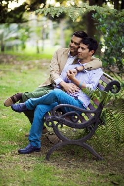 Beautiful gay couple on a park bench