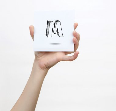 Hand holding a piece of paper with sketchy capital letter M, isolated on white.