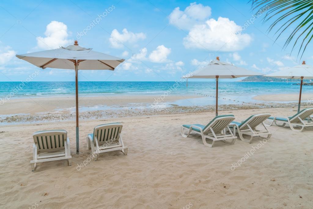 Schöne Liegestühle mit Sonnenschirm am tropischen weißen Sand beac ...