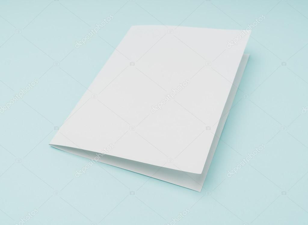 bifold white template paper on blue background stock photo