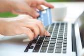 Ruce držící kreditní kartu a použití přenosného počítače pro online