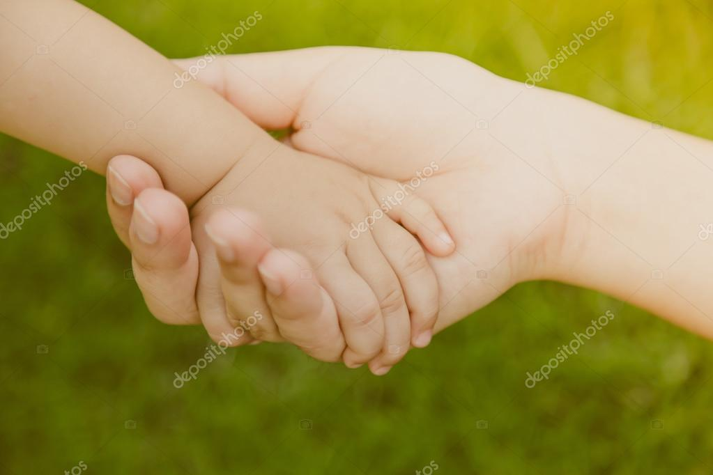 Mother holding baby hand ( Filtered image processed vintage effe