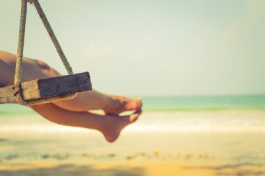 Woman  on a swing at  beach