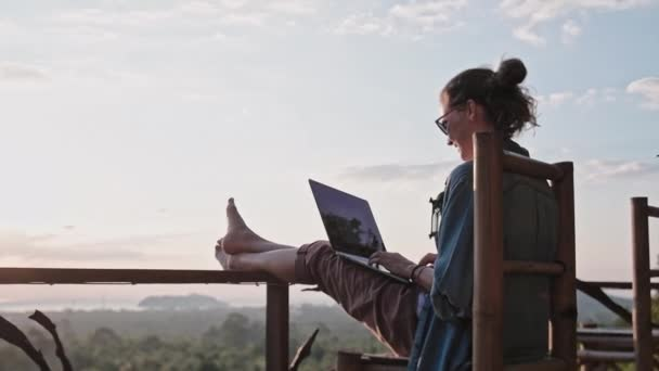 Freelancer woman sits with a laptop on a high bar chair. Amazing sunset views and dense jungle by the blue sea. A nice girl with glasses and a ponytail works on a computer in a species cafe.