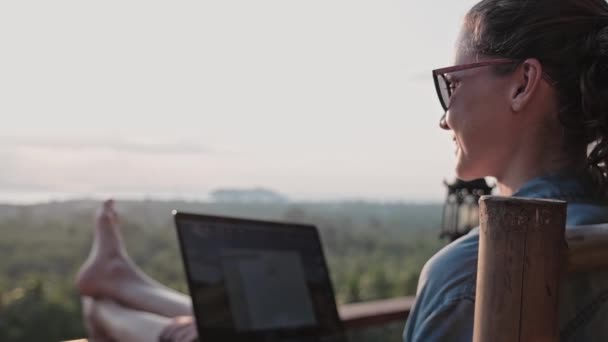 Freelancer woman sits with a laptop on a high bar stool. Amazing sunset views and dense jungle by the blue sea. A nice girl with glasses and a ponytail works on a computer in a species cafe.