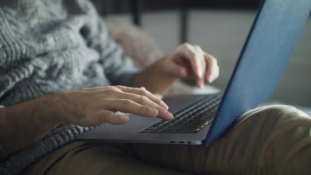 Mladý pohledný muž pracující na laptopu, zatímco leží v posteli. Muž v útulném šedém pleteném svetru uvízl na sociálních sítích. Ten mladík surfuje na internetu..