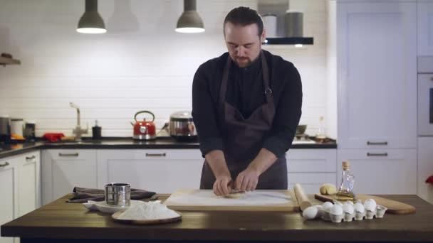Ein Mann bereitet Teig in der Küche im Haus zu.
