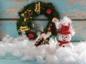 Pupazzo di neve di Natale e regali sul blu del grunge in legno decorati indietro