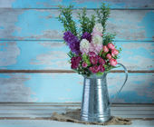 Photo A bouquet of artificial rose flowers in galvanize can set on ret