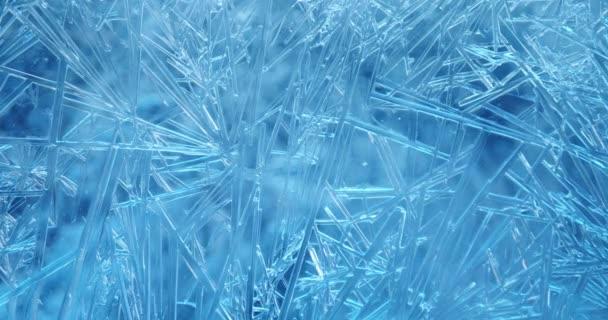 Langsamer Fokus des frostbedeckten Fensters mit Lichtern, die über Eiskristallen schimmern und glitzern.