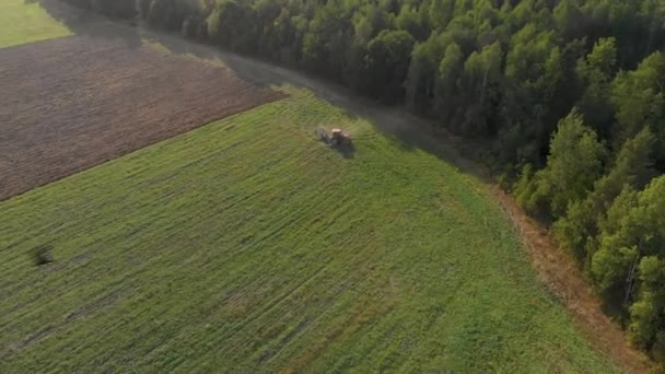 Farmer on tractor turns around near forest