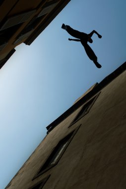 Man jumping over building roof vertical image