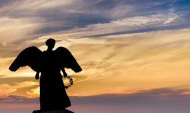 Angel sculpture on sunset background