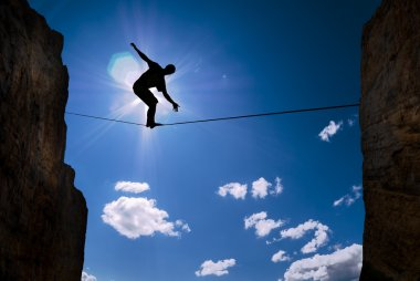Concept of risk taking man balancing on the rope