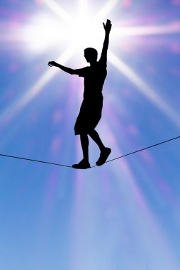 Silhouette of man on the rope concept of risk taking vertical im