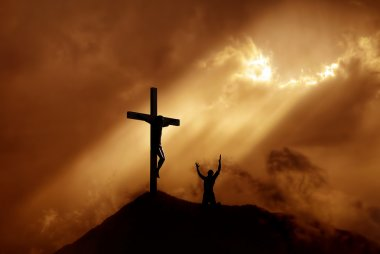 Dramatic sky scenery with a mountain cross and a worshiper