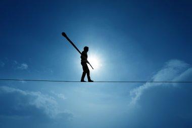 Concept of risk taking and challenge highline walker in blue sky