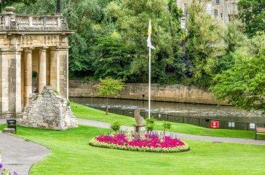 Green park and buildings along River Avon, Bath, England