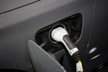 Power cable plug in charging power to electric vehicle EV car, alternative sustainable eco energy.