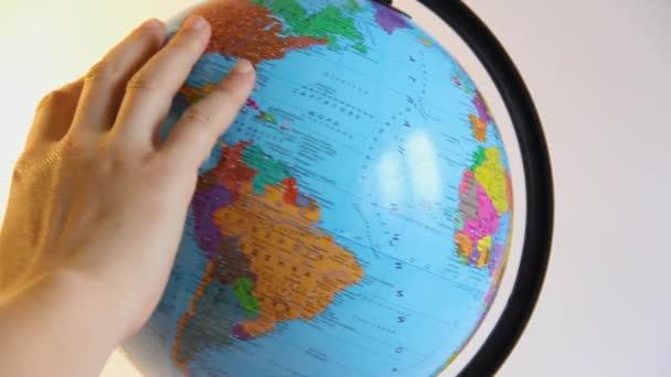 A kéz megfordítja a Földet. Kéz és földgömb