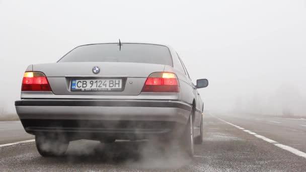 Černíkov, Ukrajina - 6. ledna 2021: Auto s rozsvícenými světlomety. Staré auto BMW řady 7 (E38) na silnici na pozadí mlhy. Smutné počasí