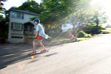 Longboarder skating on an urban road with lens flare while being filmed by another man. Slight motion blur from panning technique to capture movement stock vector