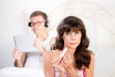 Woman Gestures Regarding Man in Bed