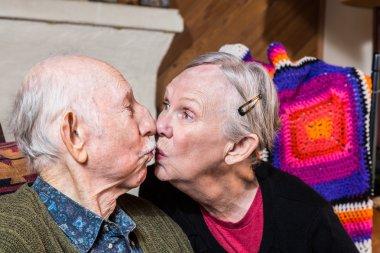 elderly couple sitting in livingroom kissing