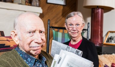 elderly husband and wife reading newspapers