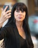žena s selfie s černý mobilní telefon