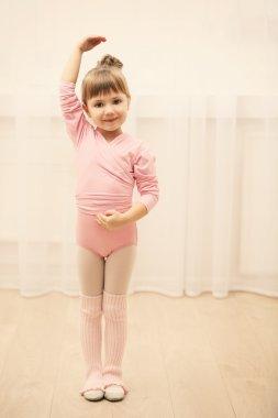 Little cute girl in pink leotard making new ballet movement at dance studio