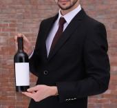 Muž, který držel láhev červeného vína v rukou