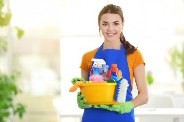 Woman in gloves holding basin with detergents