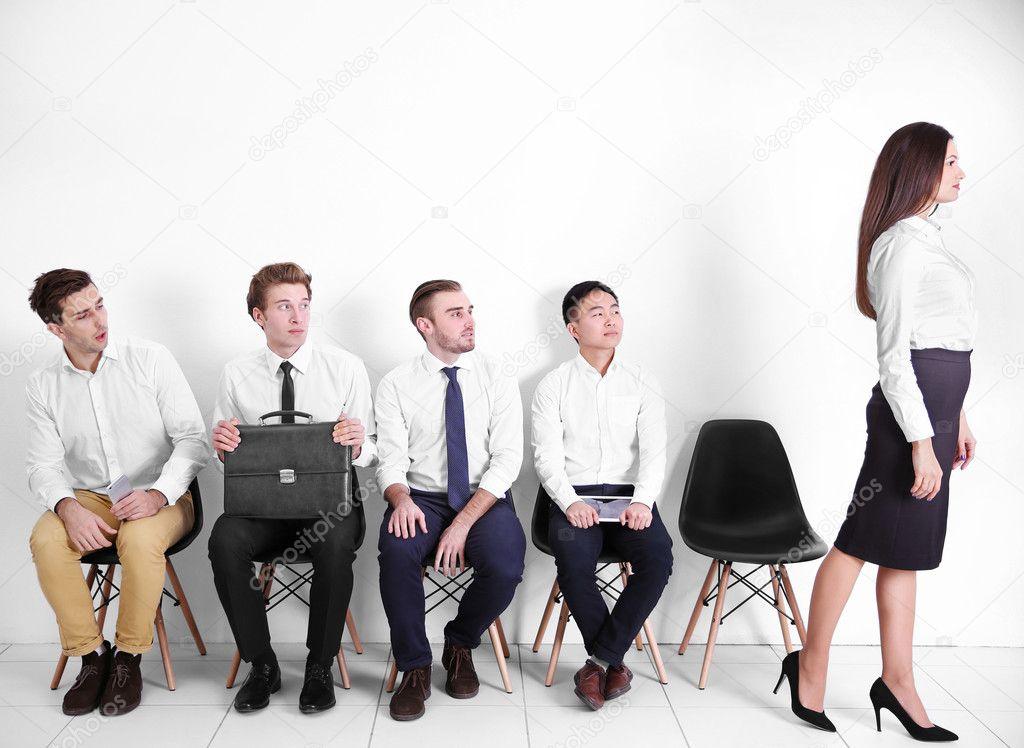 Sitzende Junge Männer Auf Der Suche Bei Frau Weißen Saal Stockfoto