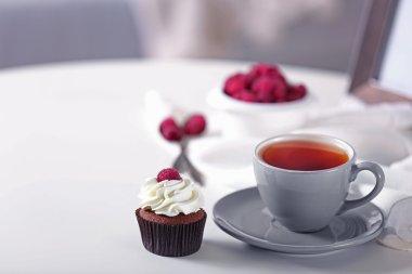 Beautiful chocolate cupcake with raspberry and tea