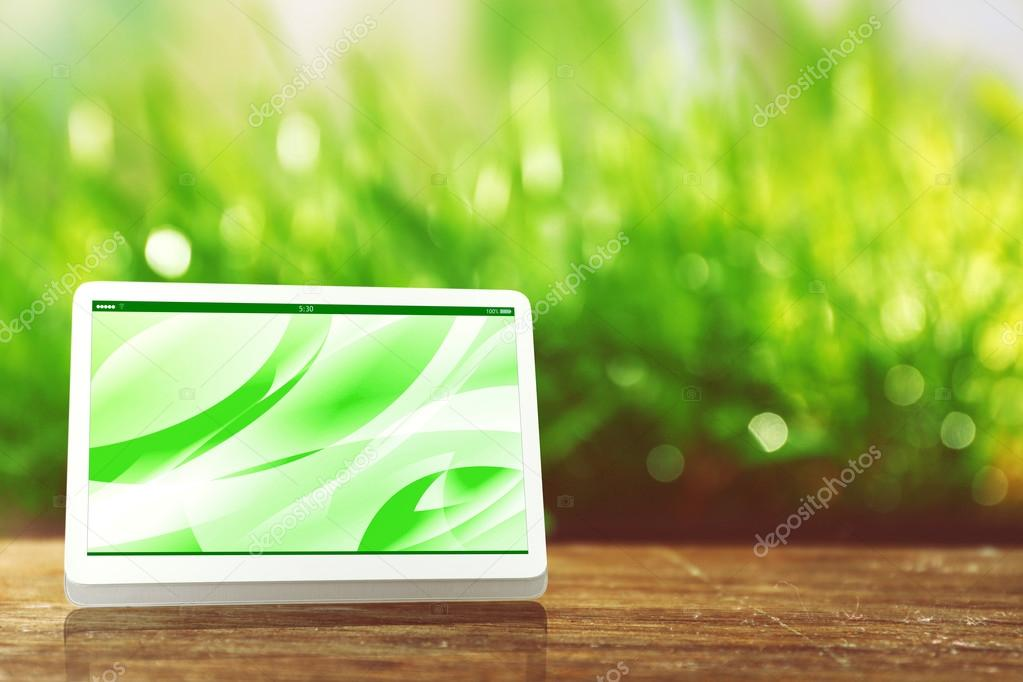 Modern tablet against green blurred grass