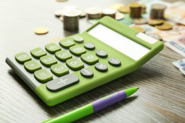 Green calculator with banknotes